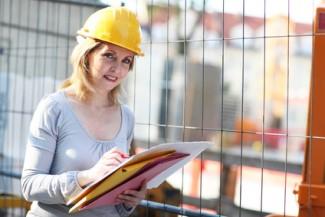 Frau mit Schutzhelm auf Baustelle