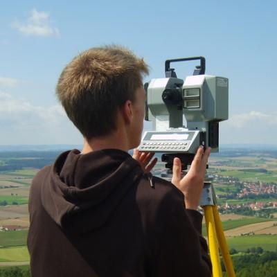 Vermessungstechnikerin Rückansicht vor Landschaft